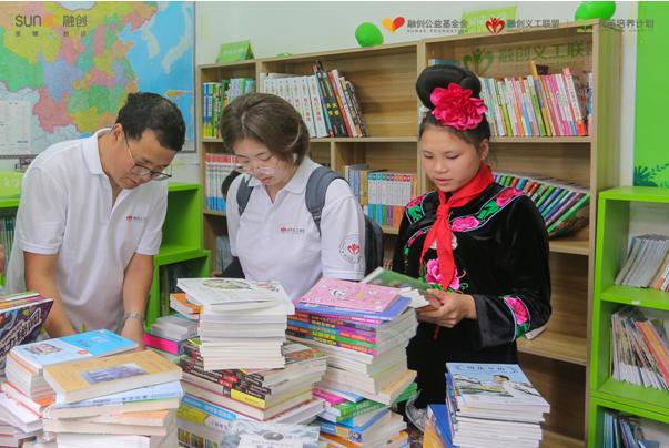 """义工把为孩子们带来新书,摆上""""英苗书屋""""盘幼书架"""