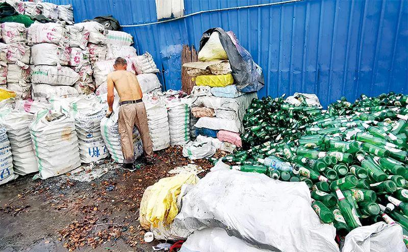 """上海军 工路附近的""""垃圾村"""",一名工人将有回收价值的玻璃瓶装袋。"""