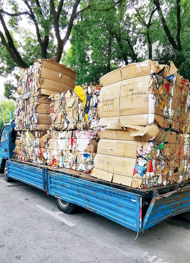 在废品站压缩打包好的废纸板,被装上卡车,等待运往下一级加工厂。
