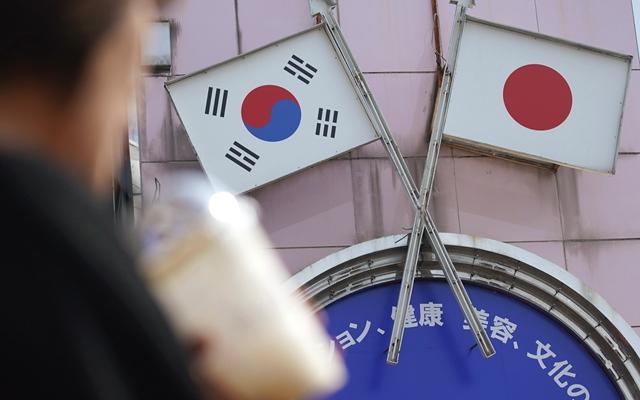 在日本首都东京的新大久保,行人从标有日本和韩国国旗的广告牌前走过。新华社