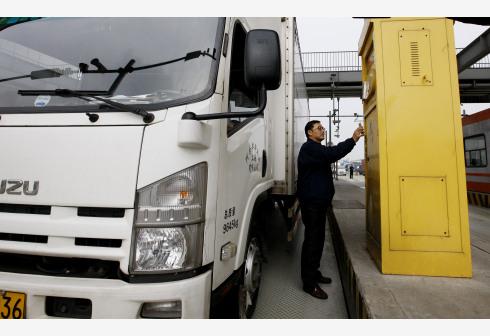 一名卡车司机在上海外高桥的自贸区车辆出入口扫描手机二维码完成通关手续(2017年1月10日摄)。新华社
