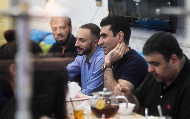 在义乌居住了近17年的阿富汗人阿兹兹(左二)在义乌的甜品店里与客商伙伴聊天。新华社