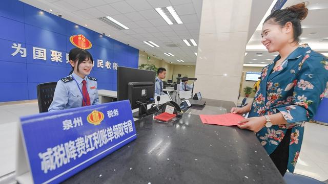 图为前来办理业务的纳税人领到工作人员送上的减税降费红利账单 新华社图