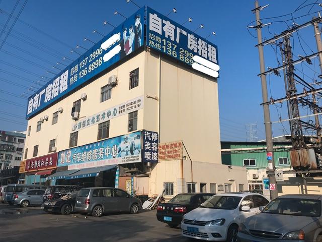 """當地人告訴記者,此前寫有""""租廠房找巨峰""""的招租廣告牌去年末換成了如今這樣無公司名稱的廣告 吳俊捷/攝"""