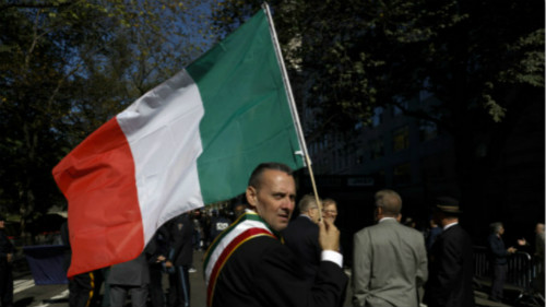 一名男子手举意大利国旗参加哥伦布日游行。哥伦布日游行是美国最大的展示意大利文化传统的庆祝活动。
