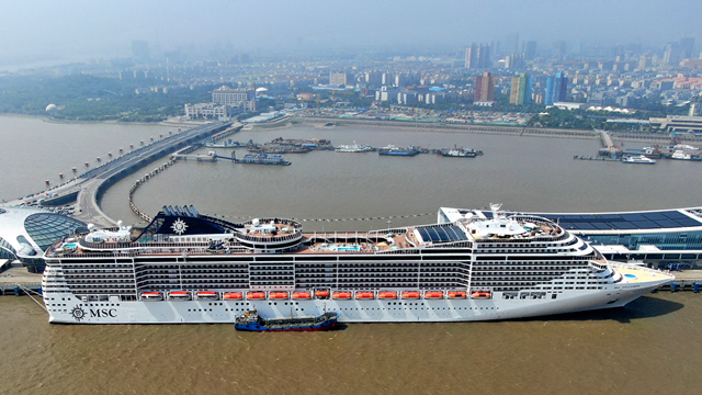 """中國首個郵輪旅游發展示范區在上海寶山揭牌,千億級郵輪產業鏈浮出水面。圖為無人機拍攝的""""地中海輝煌號""""郵輪靠泊在上海吳淞口國際郵輪港碼頭"""