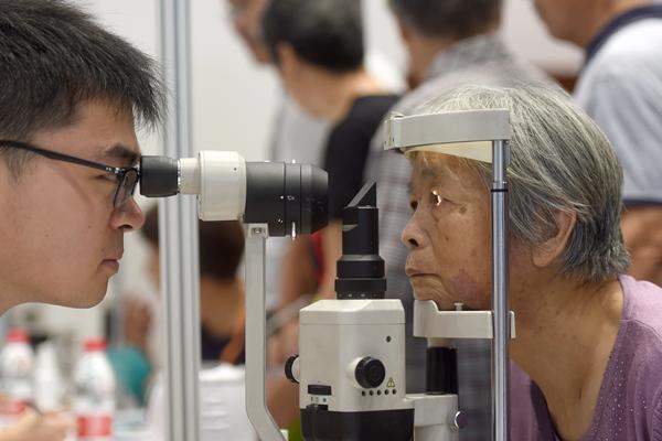 中国社会也面临老龄化问题。图为杭州一家医疗机构的工作人员(左)为老年人进行眼科义诊。新华社资料