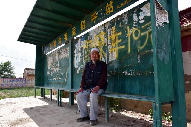 宁夏回族自治区固原市,一位老汉在村口的公交车站候车。摄影/章轲