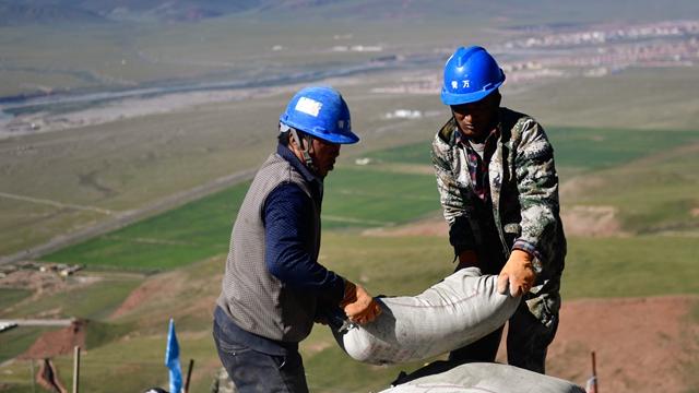 工人正在搬运水泥 新华社图