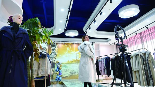 一家服装销售企业的员工正通过网络直播展示服装                               新华社图