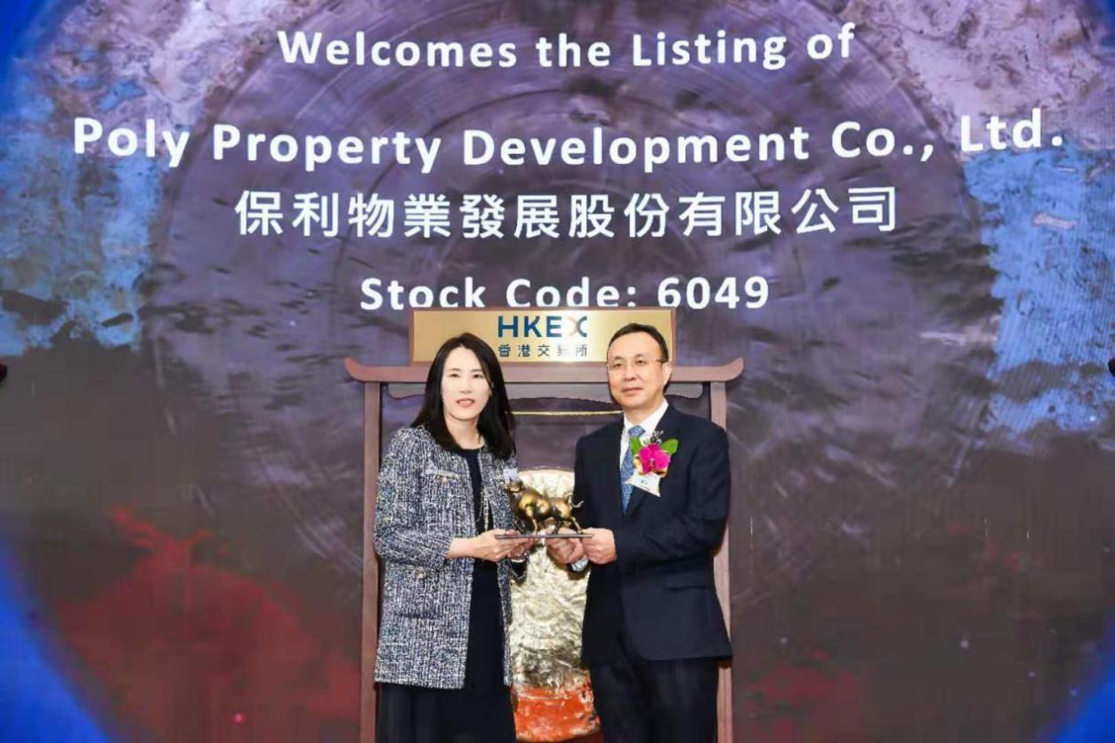 香港交易所上市委员会副主席严玉瑜,与保利发展控股集团总经理刘平交换礼物