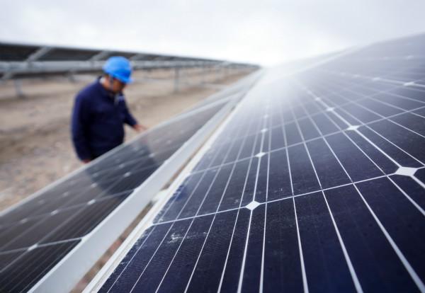 2019年10月31日,三峡新能源格尔木500MW领跑者项目工作人员查看太阳能电池组件。