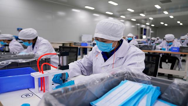 2月16日,上汽通用五菱柳州工厂无尘车间,工人在操作电焊设备,以生产口罩。(图/新华社)