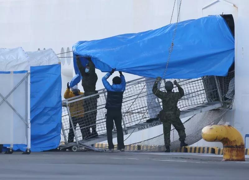 △ 2 月 10 日,做事人员用油布盖住钻石公主号的舷梯。图片来源 | 美联社