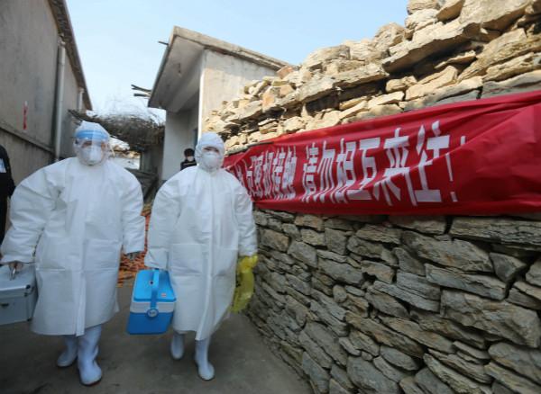 2月10日,王莉莉(左)和同事一起走街串巷做流行病学调查。新华社图