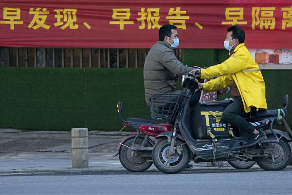 2月16日,一名市民和一名外卖员在武汉市中北路上擦肩而过 。新华社图