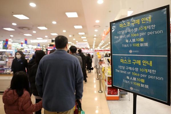 25日,韩国首尔居民在某大型超市排队购买口罩。新华社