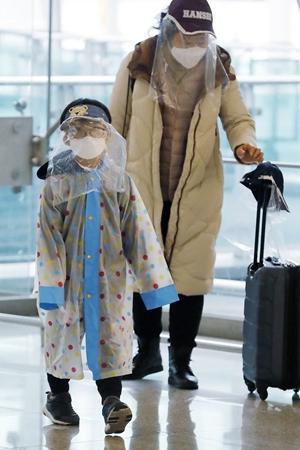25日在韩国仁川国际机场,出行的乘客采取防护措施。新华社