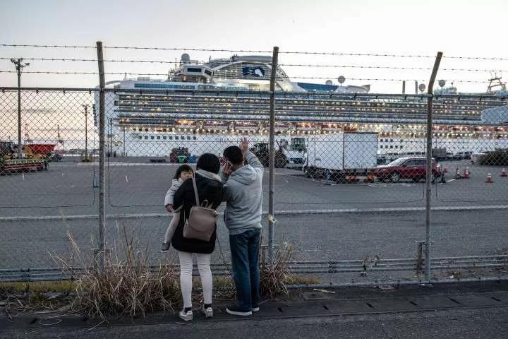 △ 2 月 11 日,一家三口向被困在邮轮上的家人挥手致意。摄影|Carl Court/Getty
