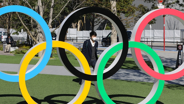 3月12日,在日本东京,一名戴着口罩的男子经过2020年东京奥运会主体育场附近的五环标志。