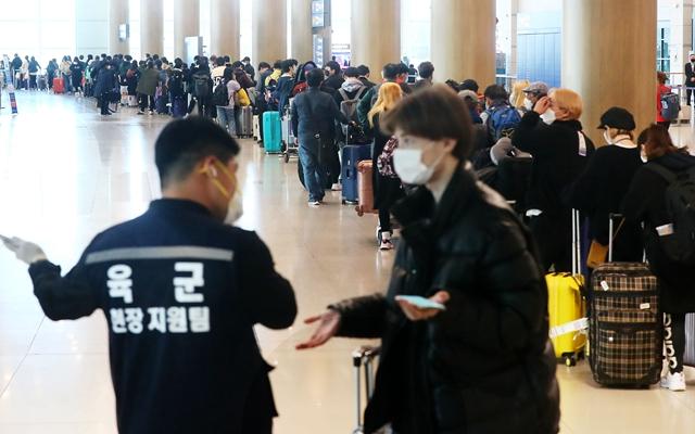 韩国仁川国际机场,等待入境的乘客们排队前往诊断隔离点。新华社