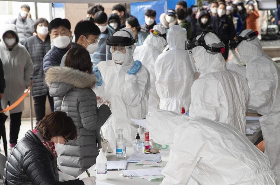 3月10日,在韩国首尔九老区,医护人员对排队进行检测的人员做登记。新华社