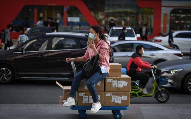 2月24日,在深圳华强北街头,一名戴着口罩的女子在打电话。新华社