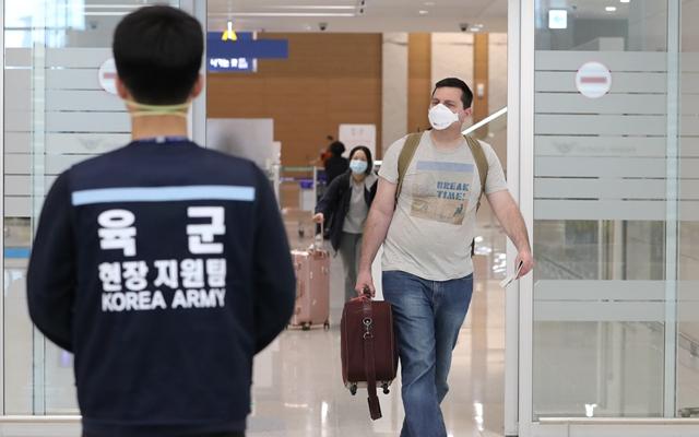 3月24日,在韩国仁川国际机场,从美国西雅图入境的乘客陆续走出行李提取大厅。新华社