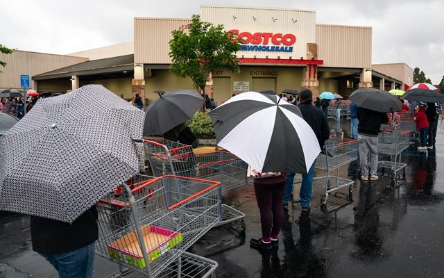 3月14日,洛杉矶附近的超市门外,人们冒雨等待超市开门进行采购。