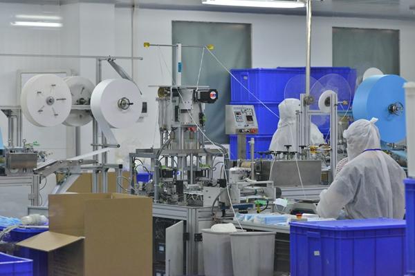 3月15日,仙桃市联赛医用产品(湖北)有限公司的工人在口罩生产线上忙碌。