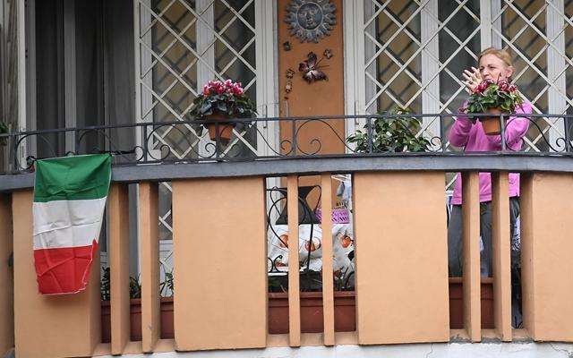 3月14日,在意大利首都罗马,一名女子在阳台参加抗击疫情的音乐快闪活动。本文图片均来自新华社