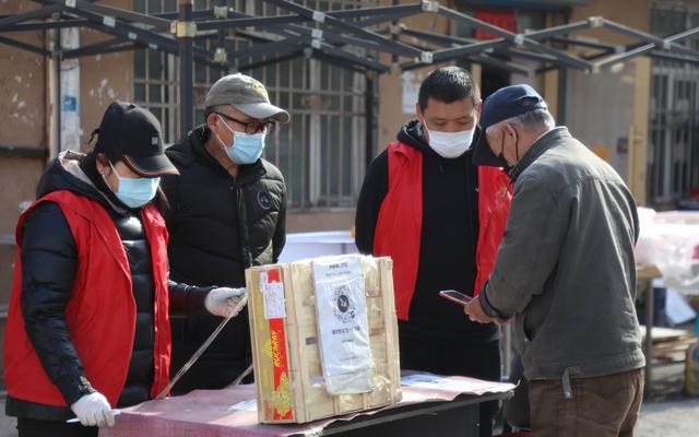 """4月10日,在绥芬河一居民小区,出入人员扫描""""健康码""""。新华社发"""