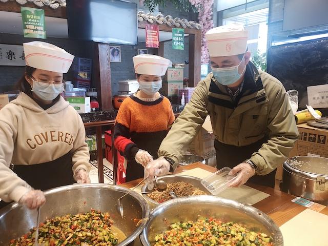 图为崔一兵(右三)和员工给抗疫一线人员配餐