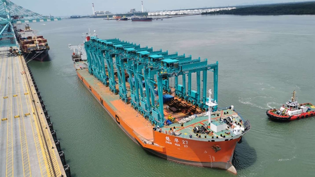 装载着10台轮胎吊的振华27#运输船成功在马来西亚新山PTP港完成卸船工作