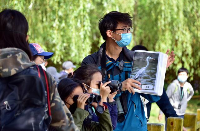 调查分析表明,公众对空气质量改善的满意度是逐渐增加的。图为5月10日一群家长和孩子在北京奥林匹克森林公园里观鸟。摄影/章轲