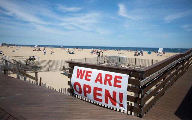 """5月16日,人们在美国新泽西州贝尔马海滩享福阳光,一家餐厅打出""""买卖中""""的招牌。新华社发"""