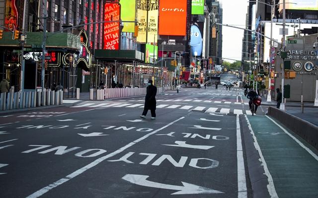 5月9日,在美国纽约时报广场,戴口罩的走人走过空旷的道路。新华社发