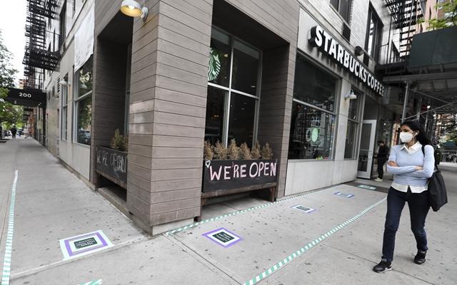 5月18日,行人从美国纽约曼哈顿一家只提供外卖服务的咖啡店外走过。新华社