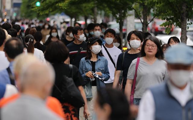 5月30日,行人戴口罩走过日本东京银座街头。新华社发