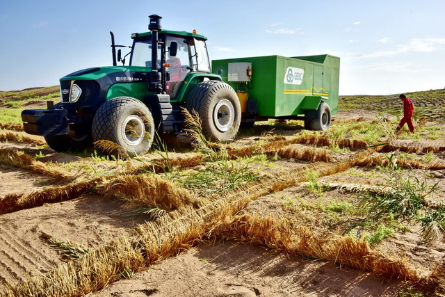 一辆多功能型立体固沙车正在甘肃省武威市某治沙试验基地进行机械设置沙障演示。摄影/章轲