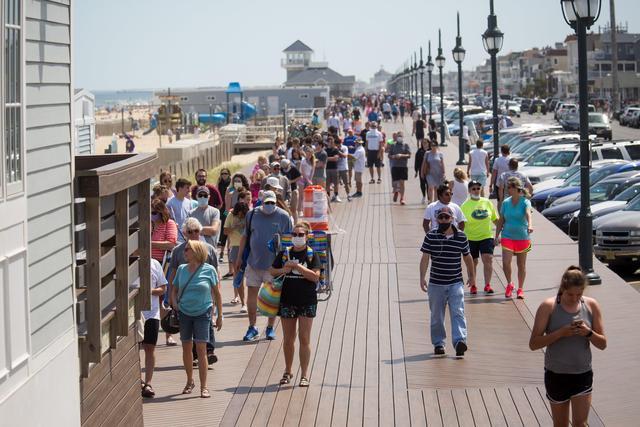 △5月16日,人们在美国新泽西州贝尔马海滩的栈道上排队等待购买海滩季票。