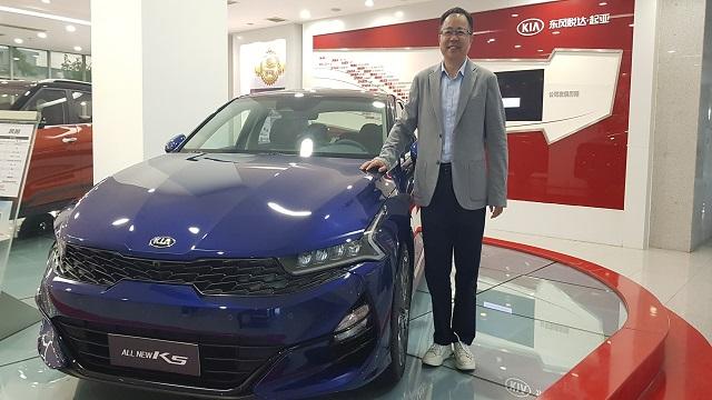 东风悦达首亚总经理李峰在批准采访前,与公司门前的车型吻合影。(图/第一财经 权幼老婆)
