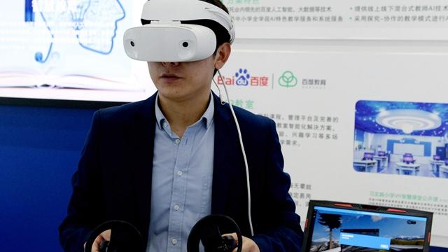 """参观者在""""中国声谷""""体验中心体验一款VR设备 新华社图"""