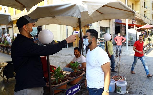 6月27日,在埃及首都开罗,别名外子进入咖啡馆前批准体温检测。新华社