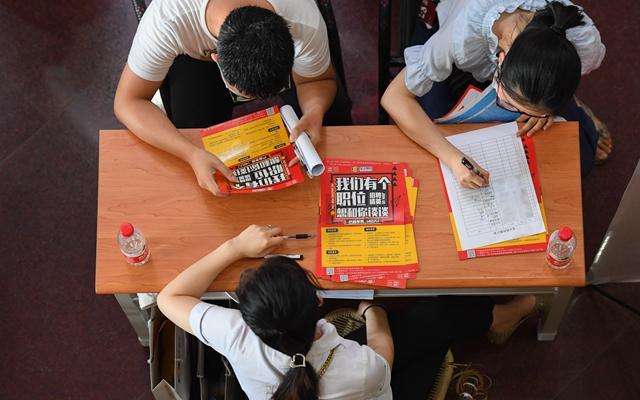 湖南一大学的学生们在招聘会上寻找合适的岗位。新华社资料图