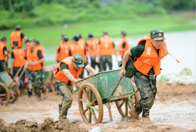 7月12日,武警江西总队机行支队官兵在鄱阳县昌江圩行使推车运送沙袋。新华社图。