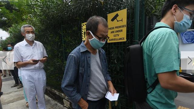 7月10日,新加坡总理李显龙(左)在一处投票站排队等待投票。 新加坡当日举行第13届国会选举。 新华社发 (邓智炜摄)