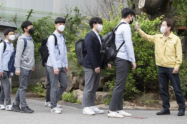 韩国首尔景福高等私塾的门生在入校前批准体温检测。新华社原料