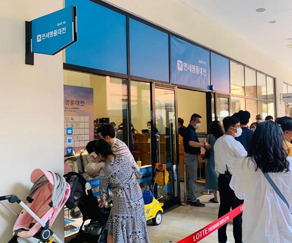 26日,韩国消耗者为进入位于笑天奥特莱斯购物中央的糟蹋品扣头专区列队期待。(受访者供图)