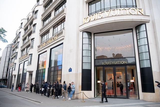 5月11日法国逐步解封。图为当天在法国巴黎香榭丽舍大街,顾客在一家奢侈品店门前排队。新华社